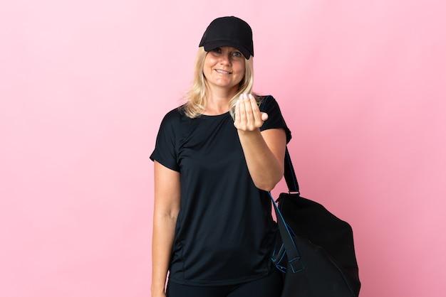 Frau mittleren alters mit sporttasche lokalisiert auf rosa einladend, mit hand zu kommen. schön, dass du gekommen bist