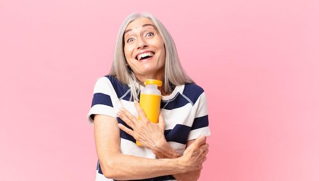 Frau mittleren alters mit weißem haar, die eine kaffee-thermoskanne hält