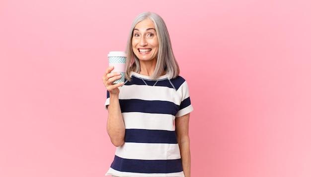Frau mittleren alters mit weißem haar, die glücklich und angenehm überrascht aussieht und einen kaffeebehälter zum mitnehmen hält
