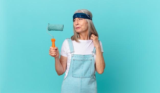 Frau mittleren alters mit weißem haar, die sich gestresst, ängstlich, müde und frustriert fühlt, wenn eine walze eine wand streicht