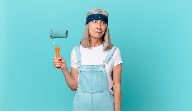 Frau mittleren alters mit weißem haar, die traurig, verärgert oder wütend ist und mit einer walze, die eine wand malt, zur seite schaut