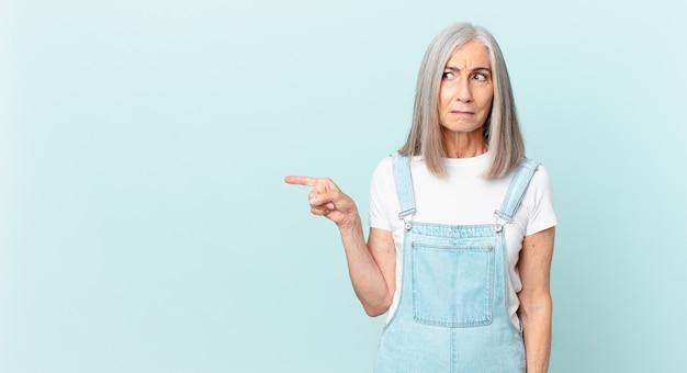 Frau mittleren alters mit weißem haar, die traurig, verärgert oder wütend ist und zur seite schaut und auf die seite zeigt