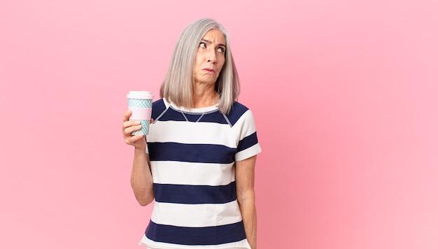 Frau mittleren alters mit weißem haar, die traurig, verärgert oder wütend ist und zur seite schaut und einen kaffeebehälter zum mitnehmen hält