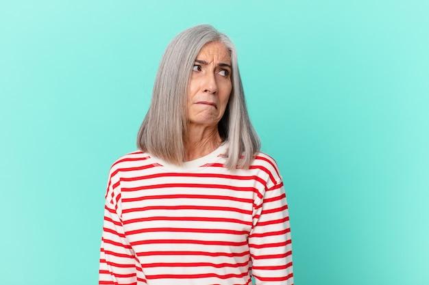 Frau mittleren alters mit weißem haar, die traurig, verärgert oder wütend ist und zur seite schaut