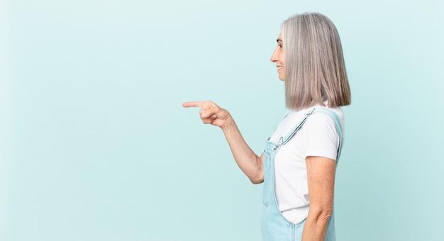Frau mittleren alters mit weißem haar in der profilansicht, die nachdenkt, sich vorstellt oder träumt und auf die seite zeigt