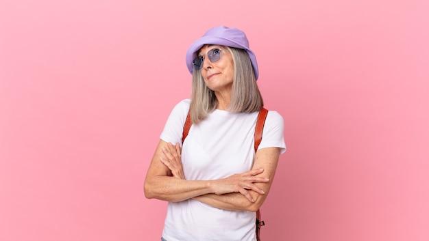 Frau mittleren alters mit weißem haar zuckt mit den schultern, fühlt sich verwirrt und unsicher
