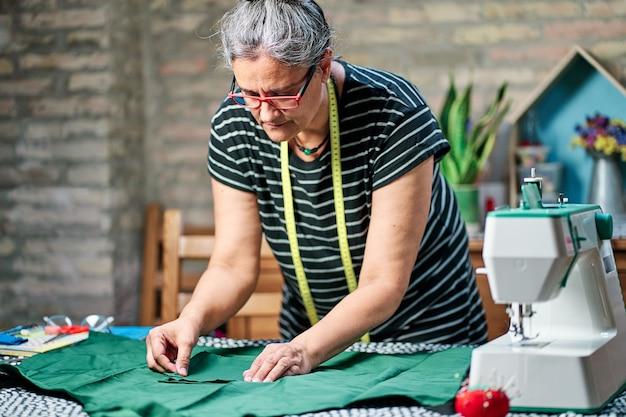 Frau mittleren alters mit weißen haaren, brille und nähband um den hals, zu hause am nähtisch arbeitend.