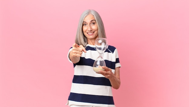 Frau mittleren alters mit weißen haaren, die einen sanduhr-timer hält