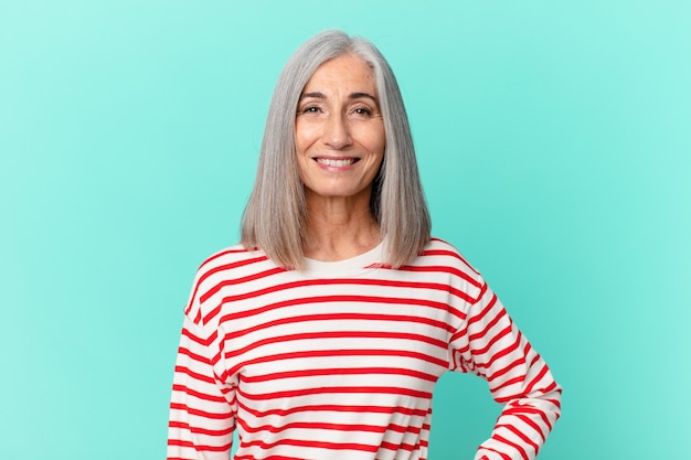 Frau mittleren alters mit weißen haaren, die glücklich mit einer hand auf der hüfte und selbstbewusst lächelt