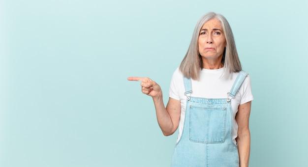 Frau mittleren alters mit weißen haaren, die traurig und weinerlich ist, mit einem unglücklichen blick und weint und zur seite zeigt
