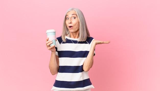Frau mittleren alters mit weißen haaren, die überrascht und schockiert aussieht, mit heruntergefallenem kiefer, die einen gegenstand hält und einen kaffeebehälter zum mitnehmen hält
