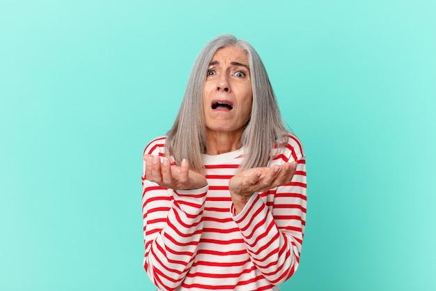 Frau mittleren alters mit weißen haaren, die verzweifelt, frustriert und gestresst aussieht