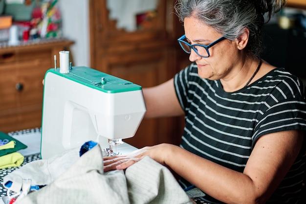 Frau mittleren alters mit weißen haaren näht mit der nähmaschine zu hause.