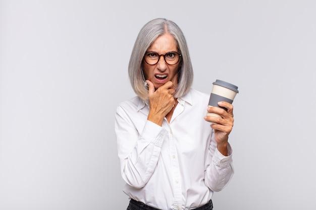 Frau mittleren alters mit weit geöffnetem mund und offenen augen und hand am kinn, die sich unangenehm geschockt fühlt und sagt, was oder wow kaffeekonzept