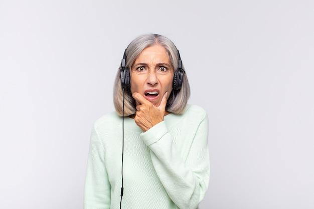 Frau mittleren alters mit weit geöffnetem mund und weit geöffneten augen und hand am kinn, die sich unangenehm schockiert fühlt