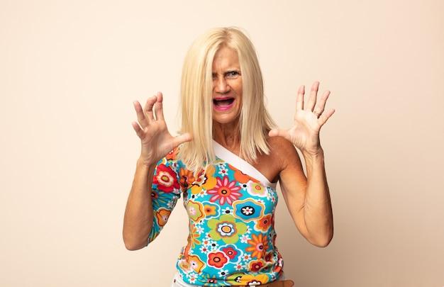 Frau mittleren alters schreit wütend, fühlt sich gestresst und verärgert mit den händen in der luft und sagt, warum ich