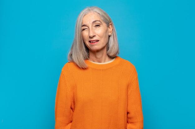 Frau mittleren alters sieht glücklich und freundlich aus, lächelt und zwinkert ihnen mit einer positiven einstellung zu