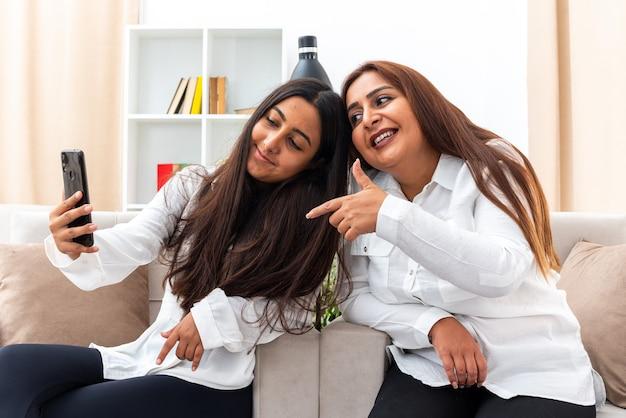 Frau mittleren alters und ihre junge tochter in weißen hemden und schwarzen hosen sitzen auf den stühlen mit smartphone mit videoanruf glücklich und positiv im hellen wohnzimmer