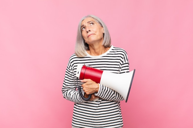 Frau mittleren alters zuckt die achseln, fühlt sich verwirrt und unsicher