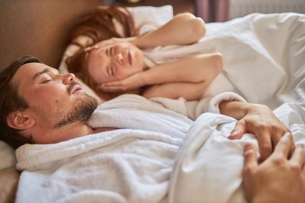 Frau müde vom hören des schnarchens ihres mannes, während sie schläft