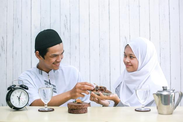 Frau muslimisch, die datteln dem muslimischen mann zur iftar-zeit gibt