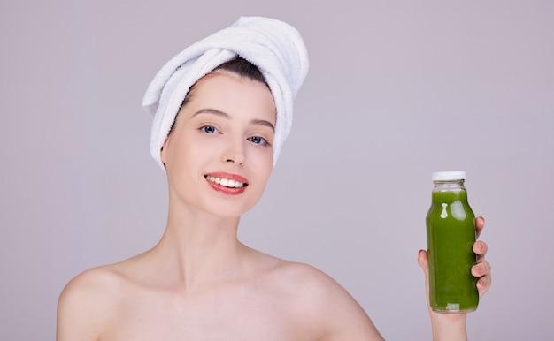 Frau nach dem duschen in einem handtuch hält in der hand einen grünen smoothie in einer flasche.