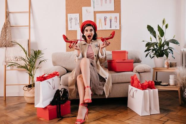 Frau nach dem einkaufen, der auf sofa mit neuer kleidung sitzt. schönes modisches mädchen hält rote moderne schuhe und sitzt auf sofa.