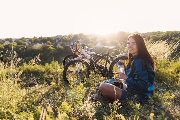 Frau nach dem fahrradfahren, das auf dem rasen sitzt