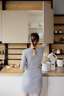 Frau nach hause, die etwas von einem küchengeschäft nimmt