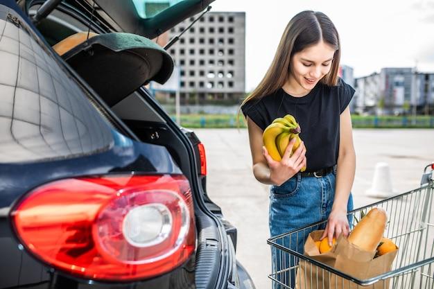 Frau, nachdem sie in einem einkaufszentrum oder einkaufszentrum eingekauft hat und jetzt mit ihrem auto im freien nach hause fährt