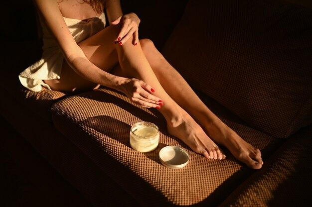 Frau nackte beine sitzen auf der couch zu hause an einem hellen sonnigen tag