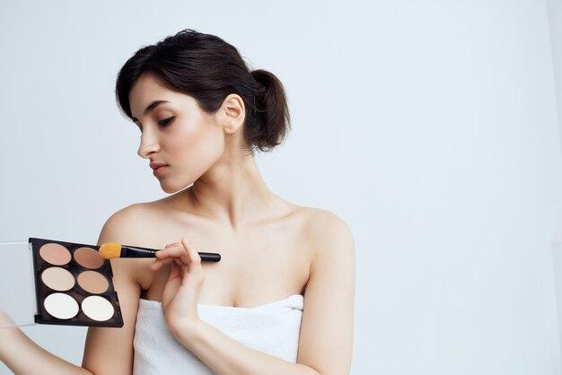 Frau nackte schultern make-up-wimperntusche-bürste. foto in hoher qualität