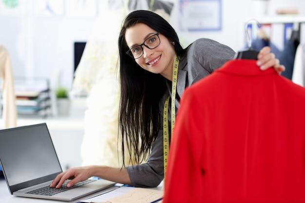 Frau näherin, die am laptop arbeitet und rote jacke hält.