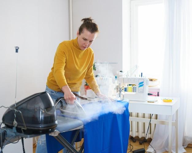 Frau näherin oder hausfrau, die stoff vor dem nähen bügelt, während sie an ihrem arbeitsplatz arbeitet
