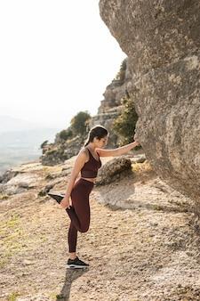 Frau nahe bei dem berg, der vor yogapraxis aufwärmt