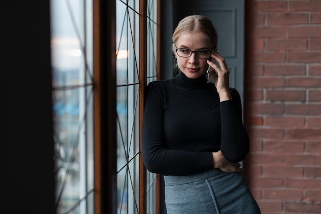 Frau nahe bei dem fenster, das über telefon spricht
