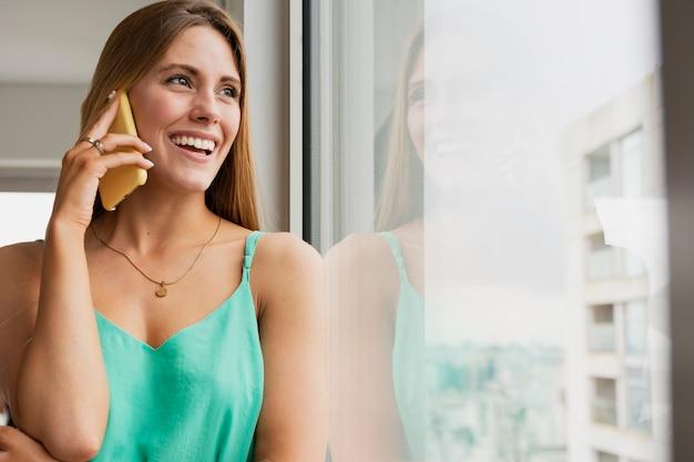 Frau nahe bei dem spiegel, der über telefon spricht