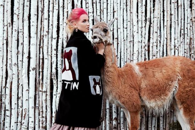Frau nahe lama im herbst auf birkenbäumen
