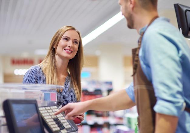 Frau neben registrierkasse im gespräch mit verkäuferin