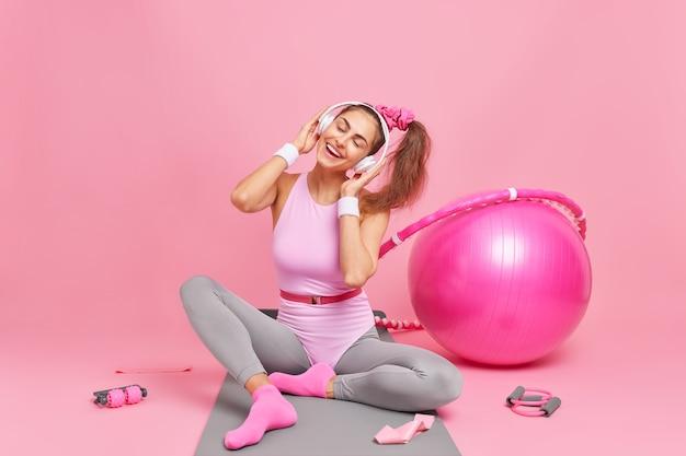 Frau neigt den kopf genießt lieblingsmelodie in aktiver kleidung gekleidet führt einen gesunden, aktiven lebensstil macht gymnastik oder aerobicbic