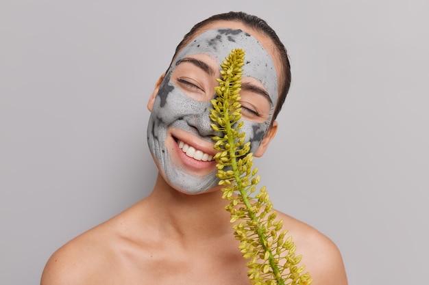 Frau neigt den kopf hält die augen geschlossen lächelt breit zeigt weiße zähne genießt die hautpflege-routine gilt nährende mitesser-porenentfernung tonmaske hält wildblumen-posen ohne hemd drinnen
