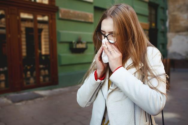 Frau niest auf der straße stehen