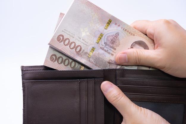 Frau nimmt banknoten von der ledernen geldbörse heraus