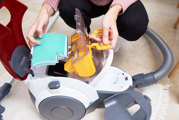 Frau nimmt behälter des staubes vom staubsauger heraus. haushaltsgeräte-service