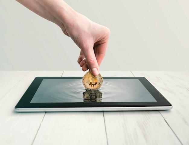 Frau nimmt bitcoin von einem tablettenschirm heraus.