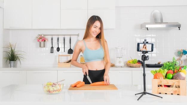 Frau nimmt das kochende video in der küche auf.