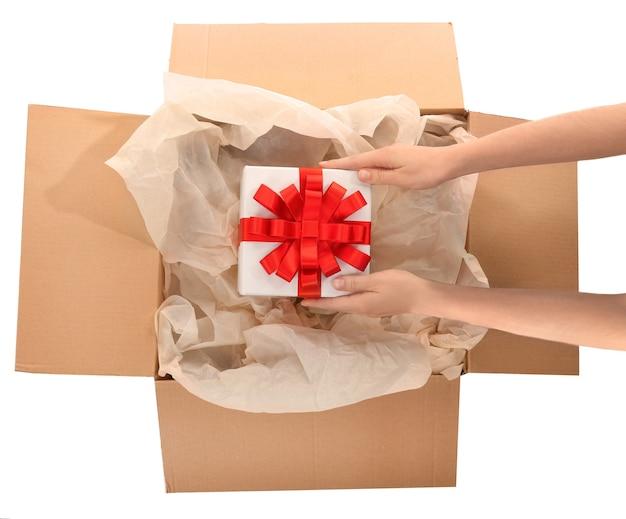 Frau nimmt geschenkbox aus paket auf weißem hintergrund