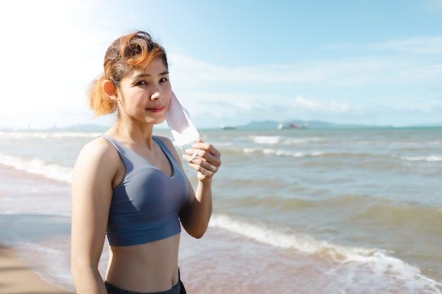 Frau nimmt maske ab und ruht sich aus, nachdem sie im sommer am strand joggt