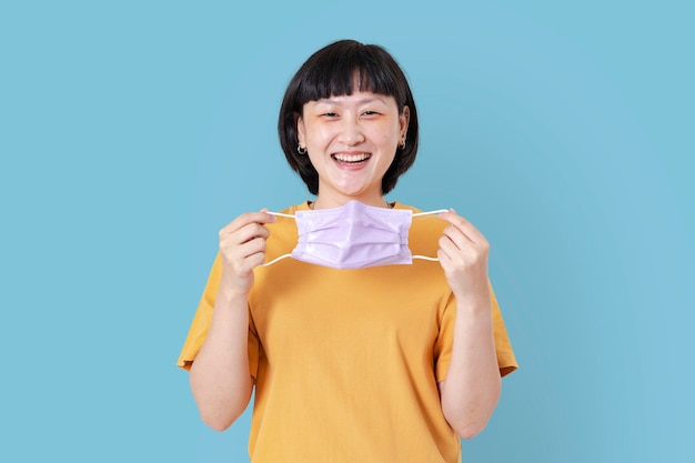 Frau nimmt maske während der neuen normalität ab