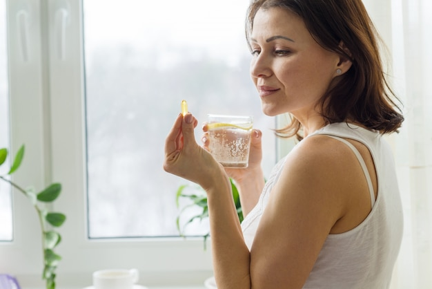 Frau nimmt pille mit omega-3